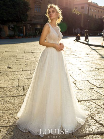 Романтичное свадебное платье по всей длине покрыто слоем полупрозрачной фактурной ткани. Она прекрасно украшает небольшое V-образное декольте, обрамленное широкими бретелями. На спинке располагается вырез, спускающийся до талии. Элегантные складки ткани по подолу придают ему дополнительный объем и украшают небольшой шлейф сзади.