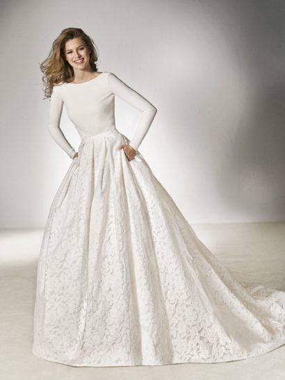 Оригинальное свадебное платье создано для невесты, способной сочетать элегантный минимализм с торжественной классикой в одном образе. Эффектный верх с длинным рукавом дополнен глубоким вырезом на спинке. Роскошная юбка со шлейфом и отделкой вертикальными складками дополнена аппликациями. Кроме того, ее украшают скрытые карманы.