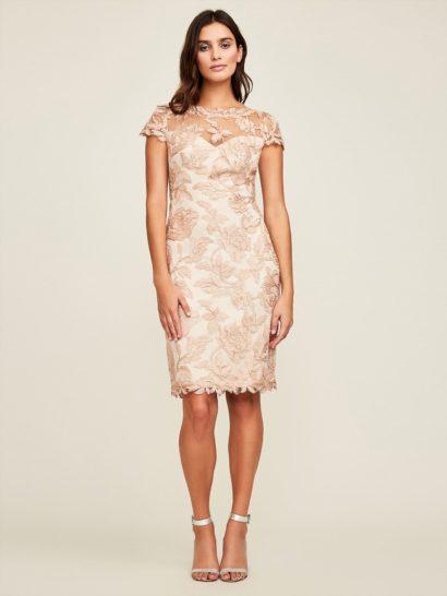 Утонченное коктейльное платье с юбкой длиной до колена прекрасно очерчивает силуэт. По всей длине оно декорировано крупными розовыми цветами кружева, оттенить которые позволяет более светлая трикотажная подкладка. Короткий рукав и полупрозрачная вставка над лифом-сердечком делают платье изящным и женственным.