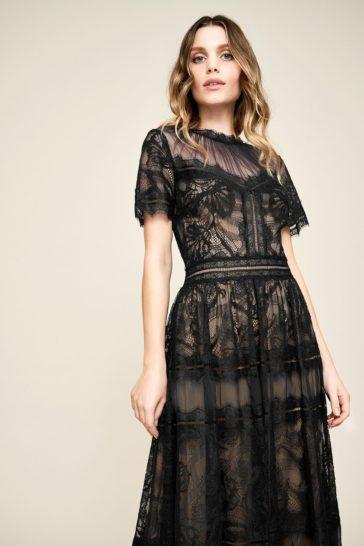 Черное вечернее платье чайной длины с короткими рукавами.