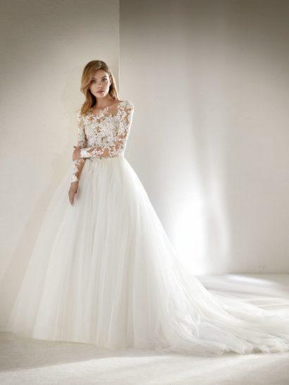 Замечательное бальное свадебное платье с эффектом двух частей.  Лиф выполнен из кружева и тюля с кристаллами и украшен аппликациями с вышивкой нитями, что создает невероятно чувственный эффект второй кожи возле выреза, на спинке и на длинных рукавах.  Многослойная приталенная юбка выполнена из тюля, что создает поистине сказочный силуэт.