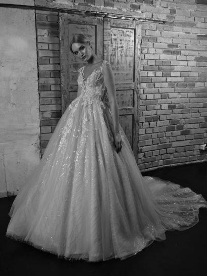 Пышное свадебное платье – воплощенная торжественность.  Эффектную красоту многослойного подола со шлейфом дополняет вышивка пайетками, кроме того, верх юбки украшают романтичные кружевные аппликации.  Открытый лиф с фигурными бретелями можно преобразить накидкой из тонкой ткани, создающей выразительное портретное декольте.