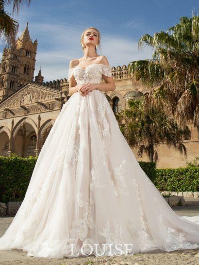 Невероятно пышное свадебное платье оттенка айвори с длинным шлейфом украшено нежными кружевными аппликациями с объемной фактурой.  Великолепный лиф портретного кроя декорирован двойными бретелями – тонкими на плечах и спущенными ниже широкими.  Спинку свадебного платья женственно украшает V-образный вырез.