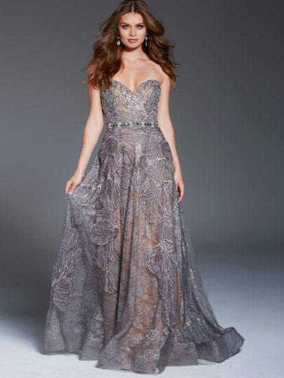 Незабываемо красивое вечернее платье впечатляет комбинацией пудрового и серого оттенков. Серая ткань с крупным цветочным узором и сияющей отделкой великолепно украшает платье по всей длине. Подчеркнуть силуэт позволяет не только открытый лиф в форме сердечка, но и узкий бисерный пояс по естественной линии талии. Многослойная юбка А-силуэта сзади складывается в шлейф.