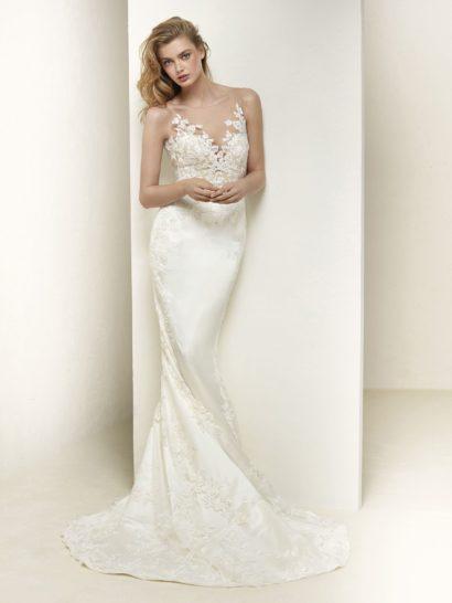 Изящество облегающего кроя силуэта «русалка» в сочетании с глянцем атласной ткани делают свадебное платье невероятно красивым. По всей длине платье декорировано мелким кружевным узором, который становится особенно выразительным на лифе с V-образным вырезом. Спинка свадебного платья обнажена притягательным округлым декольте, обрамленным тонкой тканью с аппликациями.