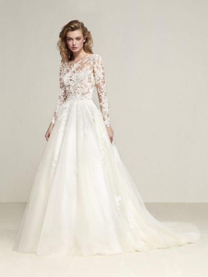 Впечатляющий объем многослойной юбки со шлейфом становится основой образа, созданного закрытым свадебным платьем.  Верх с длинным рукавом создан из прозрачной ткани, из-за чего кажется, что нежный кружевной узор покрывает обнаженную кожу.  В том же стиле оформлена и спинка.  Легкие аппликации по юбке служат прекрасными романтичными дополнениями образа.