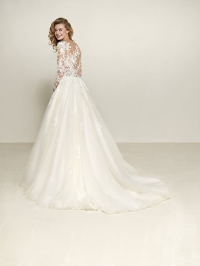 Свадебное платье пышного кроя с длинным полупрозрачным рукавом.