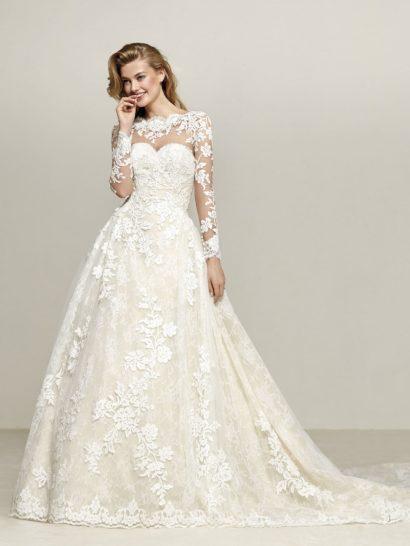 Потрясающе пышное свадебное платье с длинным рукавом создано на подкладке оттенка айвори, оттеняющей белый кружевной декор по всей длине. Образ можно преобразить, сняв полупрозрачный верх с рукавами, скрывающий лиф и спинку. Открытое платье подчеркнет область декольте выразительным декольте «сердечком».