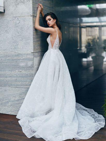 Воздушный пышный силуэт свадебного платья подчеркнут выразительными вертикальными складками по подолу и роскошным шлейфом из легкой ткани. Облегающему верху придают драматичный вид глубокие V-образные вырезы не только на лифе и на спинке, но и по бокам. По всей длине свадебное платье покрывает тонкий слой кружевной ткани.