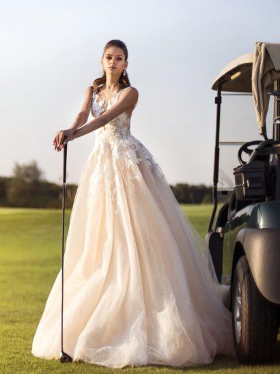 Очаровательное свадебное платье персикового оттенка создано для стильных мечтательниц. Облегающий верх декорирован плотными аппликациями белого цвета, создающими фигурные очертания соблазнительного выреза. Спинка открыта глубоким V-образным декольте. Воздушная многослойная юбка украшена вертикальными пышными волнами и шлейфом сзади.