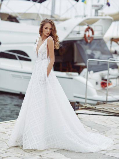 Элегантный классический силуэт «принцесса» в свадебном платье красиво сочетается с выразительной фактурой ткани. Женственная юбка дополнена не только небольшим шлейфом, но и скрытыми карманами. Притягательный лиф отличается V-образными вырезами как на декольте и спинке, так и по бокам свадебного платья.