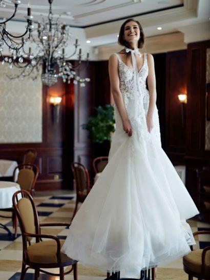 Свадебное платье с воздушной ниже линии коленей юбкой «русалка» оригинально дополнено накидкой, создающей на шее бант. Он преображает характер классического V-образного выреза, обрамленного широкими бретелями. Спинка открыта таким же декольте. Весь верх свадебного платья оформлен изящными кружевными аппликациями.