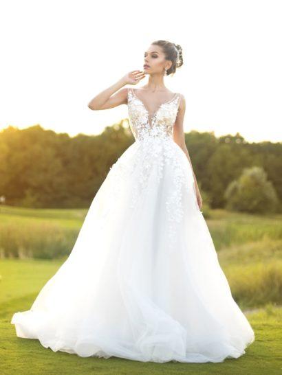 Романтичное свадебное платье с пышной юбкой грациозно подчеркивает стройный силуэт. Великолепный многослойный подол, переходящий сзади в шлейф, по верху украшают кружевные аппликации. Тем же декором отличается и лиф, созданный с иллюзией прозрачности. Он подчеркивает область декольте V-образным вырезом с широкими бретелями.