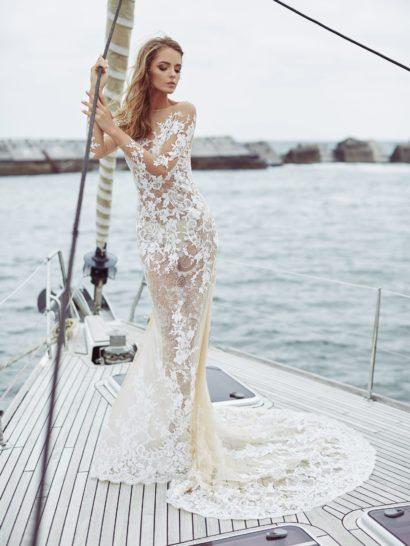 Стильное свадебное платье с иллюзией прозрачности по всей длине безупречно подчеркивает силуэт облегающим кроем. Настроение торжественности обеспечивает тонкий полукруг шлейфа с отделкой аппликациями. Игривый декор гармонично уравновешивает сдержанность линий верха – элегантное портретное декольте дополнено длинным облегающим рукавом.
