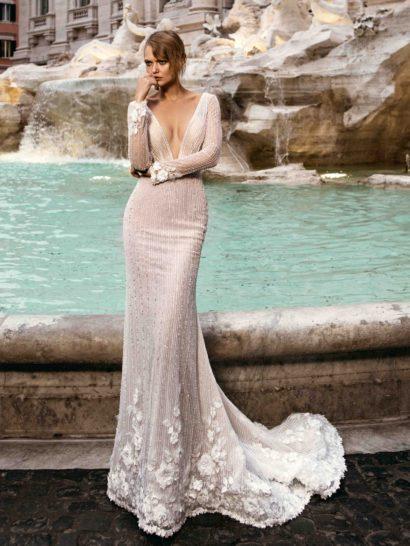 Впечатляющее свадебное платье облегающего кроя притягивает взгляд драматичным V-образным вырезом почти до линии талии.  Верх дополнен длинными рукавами, декорированными на манжетах фактурными аппликациями.  Вертикальные полосы деликатного бисера украшают силуэт, сзади дополненный элегантным полукругом шлейфа.