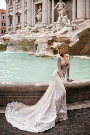 Свадебное платье с глубоким вырезом и длинным рукавом с аппликациями.