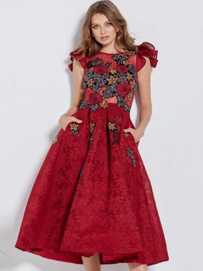 Стильное вечернее платье оттенка бургундского по всей юбке длины миди декорировано слоем кружева с цветочным рисунком. Закрытый лиф с вырезом бато декорирован оригинальными оборками на плечах. Дополнительным элементом образа служат разноцветные аппликации с вышивкой крупными сияющими бусинами. Юбку очаровательного платья украшают скрытые карманы.