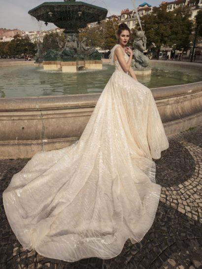 Романтичное свадебное платье оттенка айвори, подчеркивающее фигуру воздушным силуэтом «принцесса».  Облегающий корсет с лифом на тонких бретелях дополнен объемными оборками на плечах.  Они красиво обрамляют открытую спинку.  Ниже свадебное платье декорирует торжественный шлейф, спускающийся выразительной волной от линии талии.
