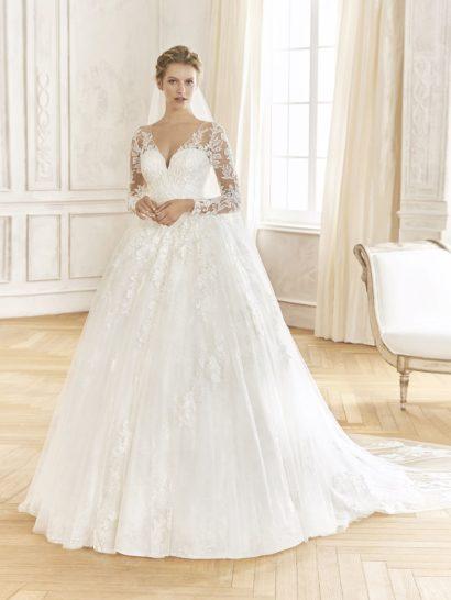 Великолепное свадебное платье пышного силуэта создает по-королевски роскошный и торжественный образ. Классические линии декольте в форме «сердечка» дополняет полупрозрачная ткань, создающая и длинные рукава. Та же ткань скрывает спинку платья. От верха и до середины подола свадебное платье нежно декорировано кружевными аппликациями с цветочным узором.