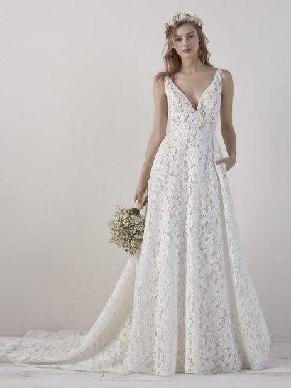 Великолепное свадебное платье А-силуэта для утонченной и романтичной девушки.  По всей длине изысканный наряд покрыт слоем выразительного кружева с цветочным мотивом.  Такая отделка прекрасно сочетается с эффектным и вместе с тем лаконичным кроем, подчеркивающим область декольте V-образным вырезом.  На спинке располагается такой же вырез, а ниже, от линии бедер, спускается пышными волнами шлейф.