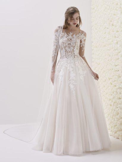Элегантное свадебное платье силуэта «принцесса» впечатляет деликатной иллюзией прозрачности, отличающей корсет. Создать ее позволяет комбинация бежевой подкладки корсета и белых кружевных аппликаций. Спинка открыта глубоким вырезом, который украшен прозрачной вставкой с вертикальным рядом пуговиц. Юбку декорируют вертикальные волны ткани и эффектный длинный шлейф сзади.