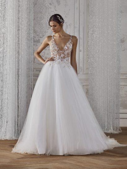 Безграничная нежность свадебного платья покорит любую невесту. В основе образа – воздушная многослойная юбка, минималистичный стиль которой только подчеркивает романтичность кроя. Верх создан с иллюзией прозрачности, обеспеченной кружевной отделкой. Глубокие V-образные вырезы на лифе и на спинке смотрятся элегантно и женственно. Роскошный шлейф гармонично завершает утонченный образ.