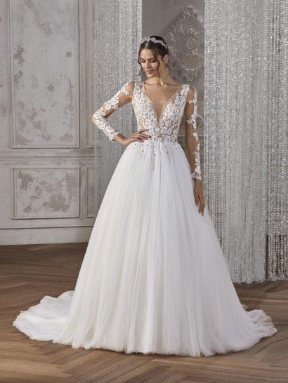 Изысканность и элегантность свадебного платья воздушного А-силуэта не могут не очаровать. Великолепная многослойная юбка украшена вертикальными волнами ткани и сногсшибательным шлейфом. Верх с глубоким V-образным вырезом, дополненным полупрозрачной вставкой, украшен стильными облегающими рукавами из тонкой ткани, по всей длине покрытыми кружевными аппликациями. Спинка выполнена из прозрачной ткани с аппликациями и пуговицами.