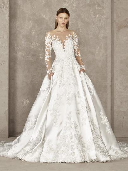 Восхитительная красота атласной ткани делает пышный силуэт свадебного платья максимально торжественным. Современные ноты классическому образу обеспечивают скрытые карманы по подолу и прозрачные облегающие рукава с кружевными аппликациями, будто бы располагающимися на обнаженной коже. Длинный шлейф, идущий от самой талии, прекрасно вписывается в элегантные линии силуэта.