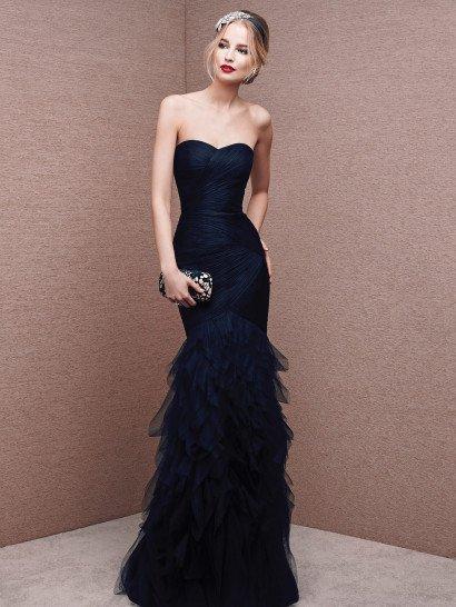 Стильный силуэт «рыбка» оригинально воплощен в драматичном вечернем платье темного синего цвета, покрытом фактурными драпировками плотной ткани, диагональными полосами подчеркивающими каждый изгиб фигуры до уровня середины бедер.  Ниже облегающая юбка покрыта пышными оборками разной длины, выполненными из полупрозрачной органзы и располагающимися друг над другом асимметричными уровнями.