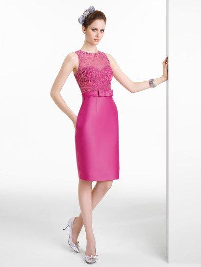 Женственное вечернее платье силуэта футляр впечатляет насыщенным розовым оттенком.  Элегантная сияющая отделка подчеркивает его выразительность.  Вышивка из бисера располагается на полупрозрачной вставке, которая скрывает лиф классической формы сердечка.  Талию лаконично выделяет широкий пояс с крупным бантом, завязанным спереди.  Юбку длиной до колена украшают лишь небольшие вертикальные швы.