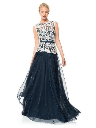 Роскошное вечернее платье выполнено из контрастных тканей графитового синего и белого цветов.  Белоснежное кружево с крупным цветочным рисунком выглядит на темной подкладке особенно выразительно, красиво скрывая открытое декольте сердечком.  Поверх кружевной ткани выделяется узкий темно-синий пояс с небольшим бантом спереди.  Многослойная юбка выполнена из воздушного шифона, придающего образу невероятную легкость.  Это платье есть в больших размерах.