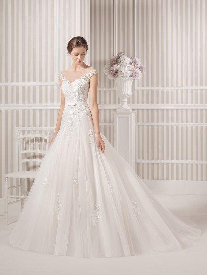 Свадебное платье с чуть заниженной линией талии элегантно обрисовывает силуэт невесты.  Открытый лиф с декольте в форме сердечка дополнен полупрозрачной вставкой, на которой располагаются кружевные аппликации, создающие фигурные бретели и покрывающие корсет.  Изящные аппликации покрывают и многослойный подол юбки из тюльмарина.  Выделяет талию узкий атласный пояс с деликатным бантиком спереди.