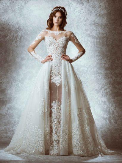 Роскошное свадебное платье А-силуэта с облегающими длинными рукавами полностью выполнено из полупрозрачной ткани на подкладке в тон кожи, создающей иллюзию обнаженности, подчеркнутую кружевными аппликациями на лифе, рукавах и на уровне бедер.  Потрясающим дополнением становится верхняя юбка из тюльмарина, украшенного кружевом, спускающаяся от линии талии по бокам и сзади, образуя шлейф.  Платье изготовлено вручную.    В НАЛИЧИИ