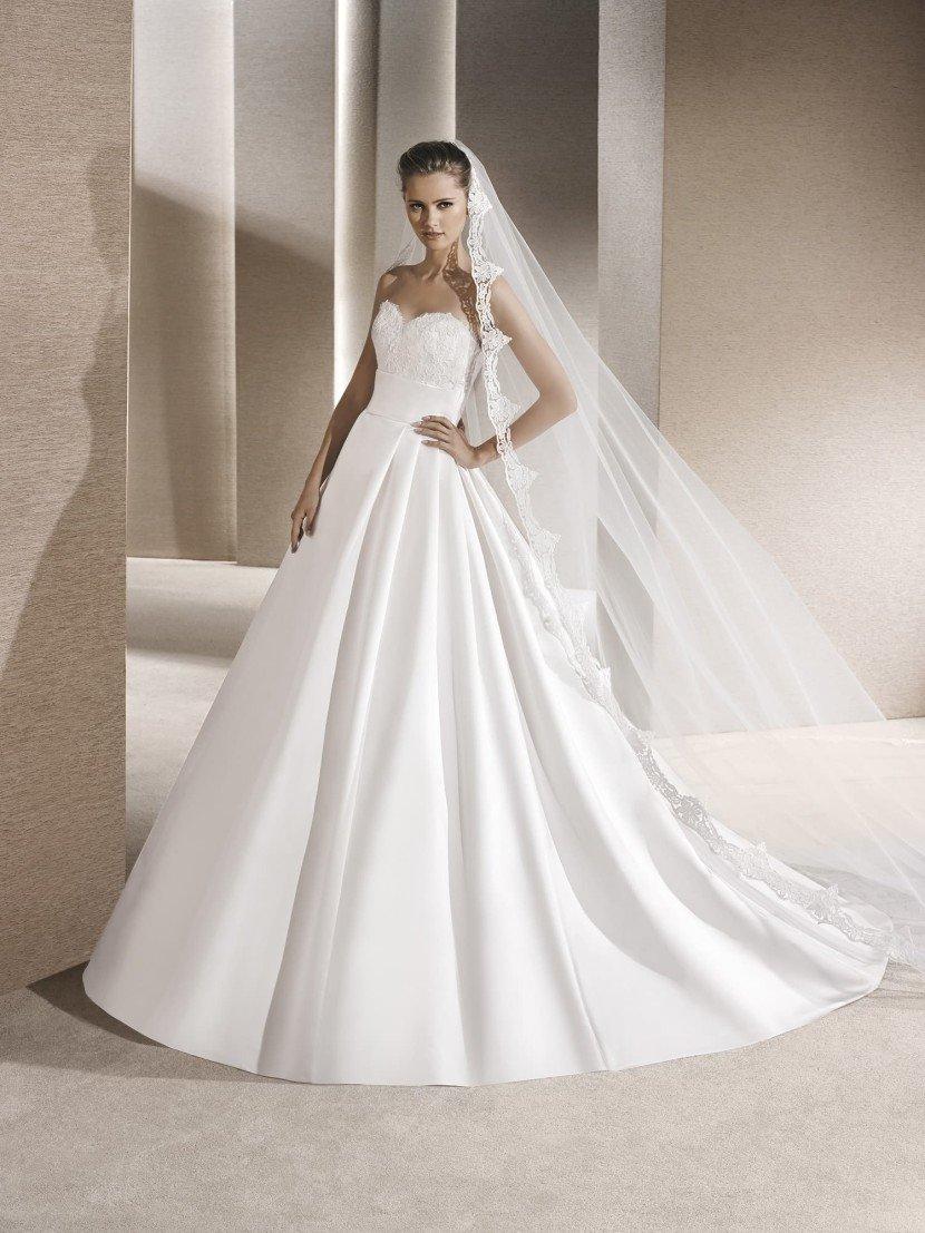 Пышное длинное атласное свадебное платье.