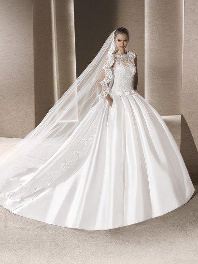 Незабываемая торжественность пышного свадебного платья заметна в каждой элегантной детали.  Юбка с потрясающим длинным шлейфом выполнена из сияющего атласа, она спускается крупными вертикальными складками.  Открытый лиф в форме сердечка сдержанно дополняет ажурная ткань, идущая от линии талии до плеч и скрывающая декольте.  Спинка украшена глубоким V-образным вырезом декольте.