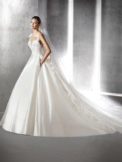 Пышное свадебное платье выполнено из глянцевого атласа и кружева.  Элегантная ткань струится объемными волнами по юбке, складываясь торжественным шлейфом.  Кружевная ткань декорирует весь верх, от талии, обрисованной узким атласным поясом, и до плеч, покрывая декольте в форме сердечка.  Спускаются кружевные аппликации и по пышной юбке, украшая шлейф вертикальными полосами цветочного узора.
