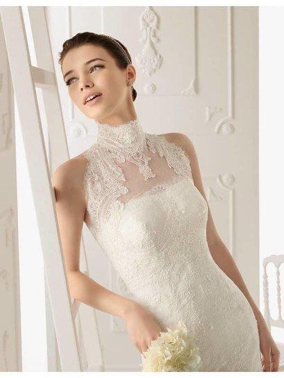 Эффектное недорогоеоткрытое кружевное свадебное платье с роскошным шлейфом, зафиксированным сзади на линии талии оригинальной бутоньеркой.  Наряд дополнен съёмным жакетиком с кружевной аппликацией.  Воротник-стойка и американская пройма кардинально меняют образ.  Серебристая тиара украшена кристаллами и жемчужинами.