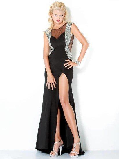 Стильное узкое длинное вечернее платье из чёрного трикотажа, вырез «лодочка», рукава «крылышки», спереди - высокий разрез.  Область декольте, боковые части и спинка - из прозрачной ткани.  Декор из крупного серебристого бисера украшает плечи, линию проймы, очерчивает силуэт по бокам и переходит на спинку.