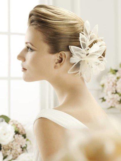 Кокетливое украшение для свадебной прически создано из полупрозрачной белой ткани. Несколько лаконичных бутонов с объемными лепестками складываются в романтичную и эффектную композицию.