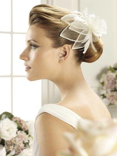 Эффектная заколка для свадебной прически наполнит образ романтичным настроением. Заколка выполнена в виде крупного цветочного бутона с объемными листьями из полупрозрачной белой ткани. Такой аксессуар подойдет для разных видов укладки.