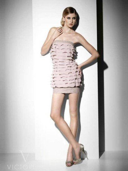 Стильное открытое прямое короткое вечернее платье на выпускной из коллекции вечерних платьев линии «It's my party» Pronovias Fashion Group.  Полосы эластичного кружева по линии декольте и подолу надёжно удерживают горизонтальные ярусы воланов.