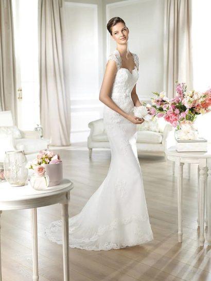 Изысканное кружевное свадебное платье прилегающего силуэта.  Крой рукавов-крылышек и изгиб верхнего края лифа создают сложную форму декольте «королевы Анны».  Высокая застёжка на спинке, скрытая цепочкой пуговиц, создаёт дополнительный декор на ажурном рисунке. Естественная линия талии подчёркнута узким пояском-лентой с деликатным бантиком по центру переда.  Свадебное платье от Pronovias Fashion Group.