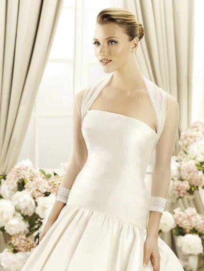 Свадебное болеро с рукавами в три четверти из коллекции 2014 бренда LaSposa Pronovias Fashion Group.  Склады прозрачного тюльмарина формируют шалевый воротник. Манжеты, украшенные стразами, декорируют край рукавов.  Эта модель болеро подойдёт к свадебному платью из любой ткани.