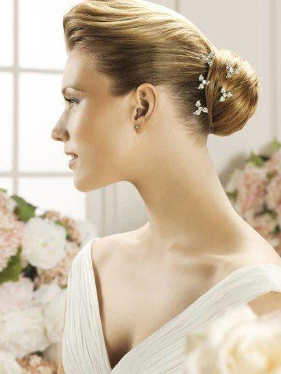Эффектная заколка для свадебной укладки привлекает внимание блеском стразов и оригинальным решением. Композиция складывается из нескольких маленьких цветочных бутонов из серебристого металла.