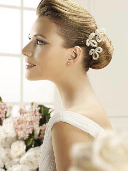 Интересная заколка позволит придать особенное очарование любой свадебной укладке. Она выполнена в лаконичном стиле и представляет собой несколько бутонов с простыми округлыми лепестками, украшенных в середине серебристыми стразами.