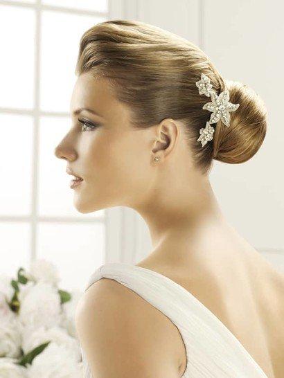 Несколько изящных бутонов кремового цвета смогут романтично дополнить свадебную прическу. Лаконичные очертания цветов из плотной ткани повторяют линии из крупных серебристых стразов, украшающие каждый бутон.