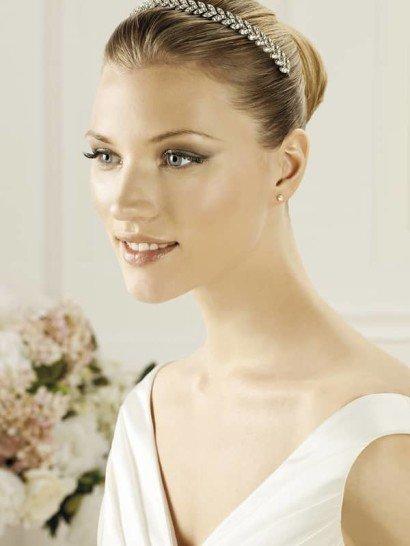 Стильный обруч для свадебной укладки, который прекрасно подойдет к платьям в ампирном стиле. Средней ширины линию создают лаконичные листья, расположенные в два ряда и выполненные из небольших сверкающих стразов серебристого цвета.