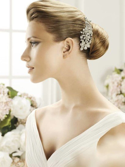 Женственная красота сверкающей заколки гармонично будет смотреться в сочетании с элегантной укладкой невесты. Крупный серебристый аксессуар покрыт стразами разных размеров, гарантирующими эффектный блеск при каждом движении.