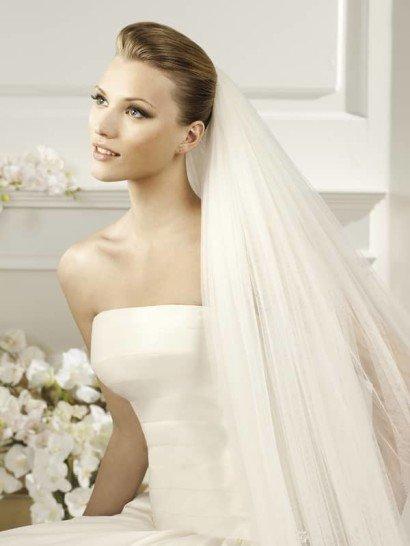 Широкая 6-ти метровая полоса еврофатина, сложенная вдвое, образует полупрозрачную фату, деликатно украшенную объёмными крапинками. Густая сборка фаты из коллекции испанской марки La Sposa Pronovias Fashion Group, закреплённая наверху высокой причёски, придаёт образу невесты выразительный акцент и формирует полосу второго шлейфа. Прекрасное дополнение к стильному свадебному платью из пластичного шифона.  Размер 3x6м