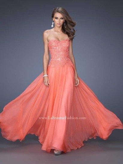 Это стильное платьенежно-кораллового цвета - прекрасный выбор для выпускного вечера.  Открытый лиф с плавной линией декольте в форме «сердечка» покрыт романтичным кружевом в тон ткани, расшитым мерцающими кристаллами.  Заниженная линия талии, фиксирующая широкую летящую юбку, формирует мифический силуэт сказочной красоты.